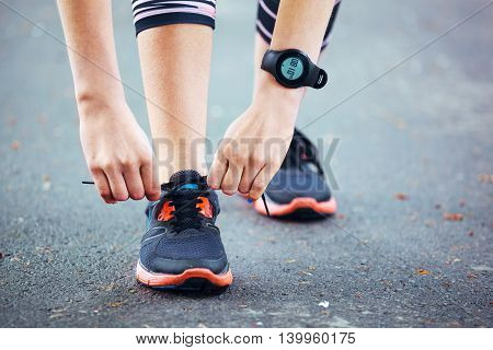 Close Up Of Young Woman Tying Her Laces Before A Run.