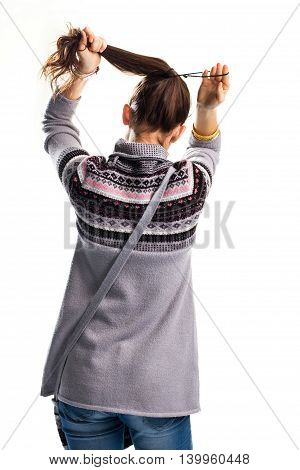 Lady is tying hair. Back view of gray sweatshirt. Casual clothing and simple hairdo. Style for spring.