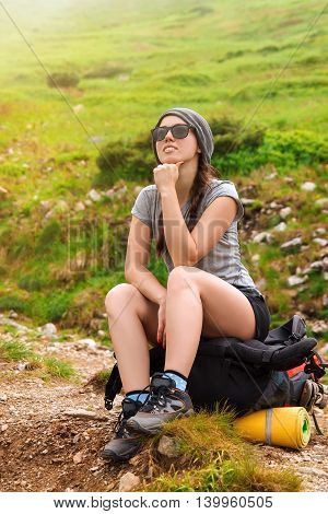 Girl tourist sitting on a backpack in mountain. Lifestyle concept active leisure tourism. Woman hiker