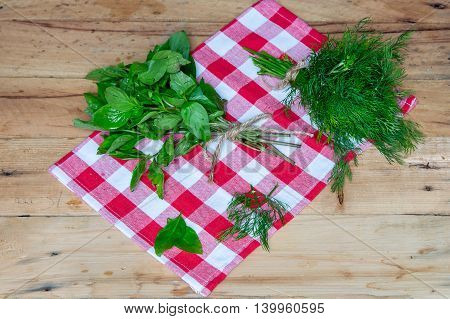 Fresh dill and  basil on wooden table. Top view.