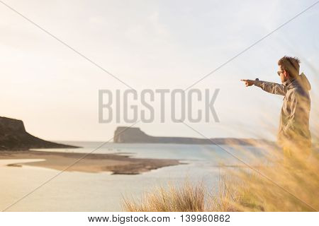 Sporty active man pointing hand on island on horizon, enjoying beauty of nature, freedom and life at beautiful landscape. Active lifestyle outdoors.