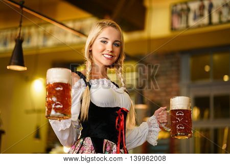Young waitress with beer mugs