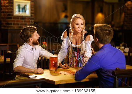 Young men and waitress in a pub