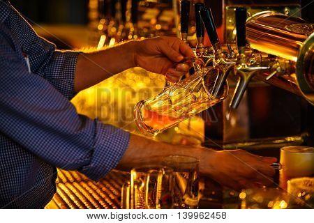 Bartender pours a beer indoors