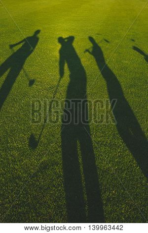 Silhouettes of golfers with clubs on grass, vertical image
