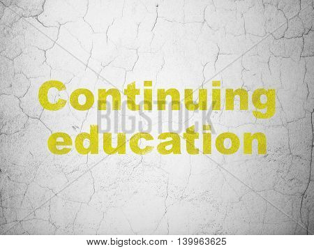 Studying concept: Yellow Continuing Education on textured concrete wall background