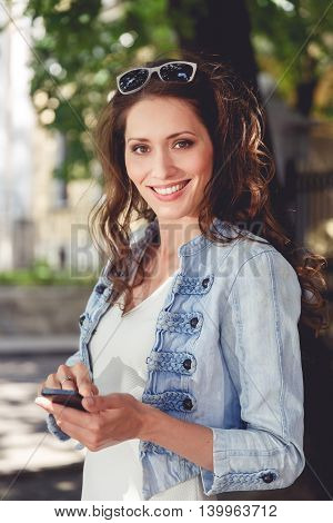 Smiling brunette woman in white dress and blue denim jacket holding smartphone outdoors
