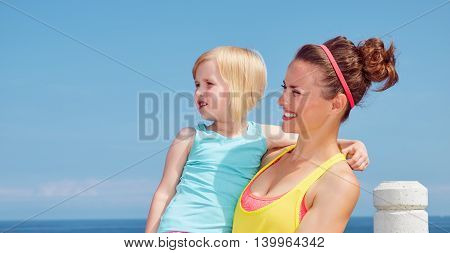 Happy Mother And Child In Fitness Outfit On Embankment