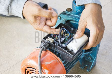 Electric motor  and man working equipment repair on cement floor background.Backgroud motor or equipment.Zoom in 00