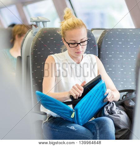 Businesswoman sitting and traveling by train working on laptop. Business travel concept.