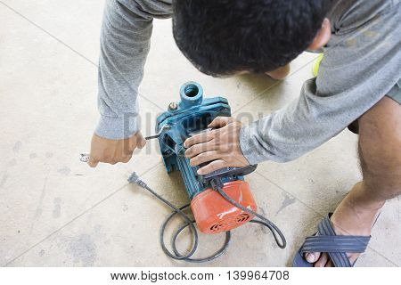 Electric motor  and man working equipment repair on cement floor background.Background motor or equipment.Zoom in 01