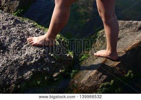 Watersports in water droplets, bare feet of young girl walk on huge gray boulders overgrown with weeds, lying in sea
