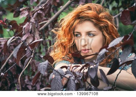 Girl with red hair and blue eyes looking to the left surrounded by black cherry plum leaves
