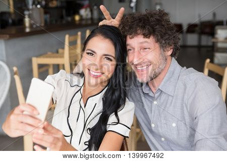 Happy couple taking a selfie in cafeteria
