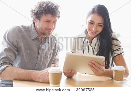 Couple using digital tablet in cafeteria