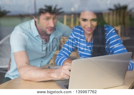 Happy couple using laptop in cafeteria