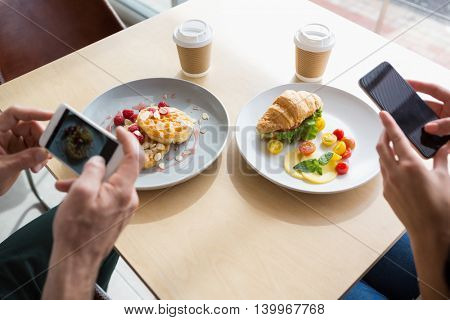 Couple taking a photo of their snacks in cafeteria