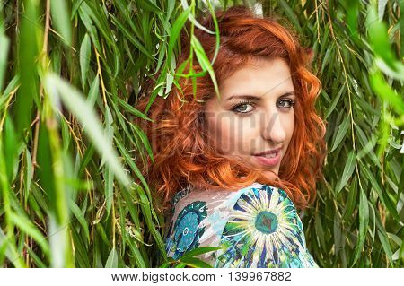 Girl with red curly hair looking over her shoulder surrounded by weeping willow leaves