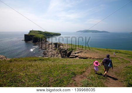 Mother with her daughters walking near sea