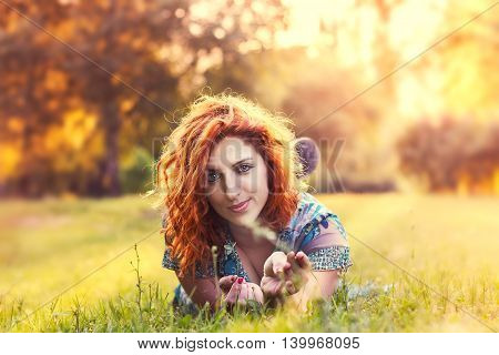Girl with red hair and blue floral dress lying on her stomach in the park. Plenty of copy space