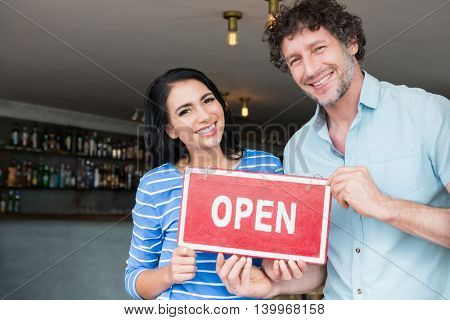 Portrait of happy couple holding open signboard in cafeteria