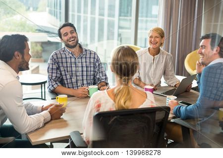 Business people holding coffee mug during a meeting in the office