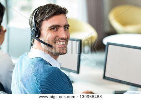 Portrait of a young man working on computer with headset in office