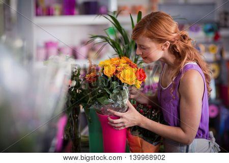 Female florist smelling flower bouquet in the flower shop