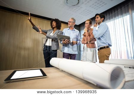 Woman framing with hand while standing in board room with colleagues at office