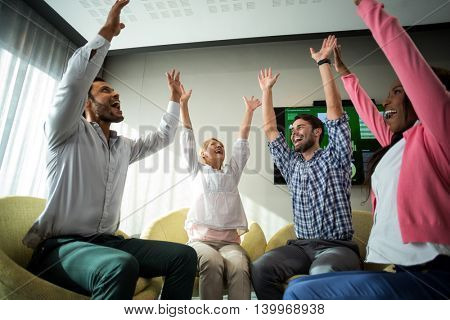 Business people raising their arms during meeting in the office