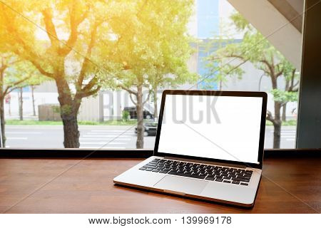 Laptop with blank screen on table with Osaka background