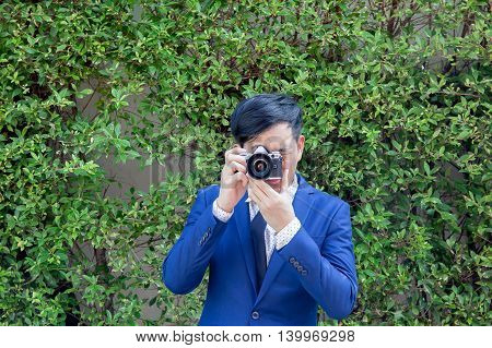 Asian Professional Photographer Take Photos In Green Background