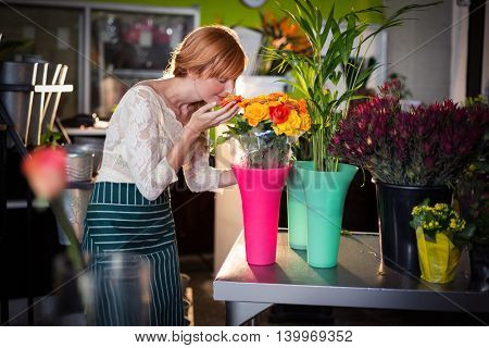 Portrait of female florist smelling rose flowers in the flower shop