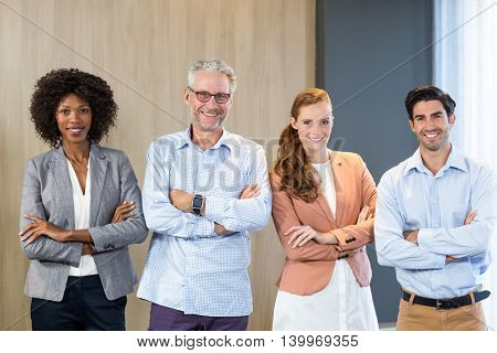 Portrait of smiling business people standing together with arms crossed in office