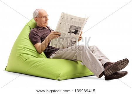 Joyful senior reading a newspaper seated on a comfortable green beanbag isolated on white background