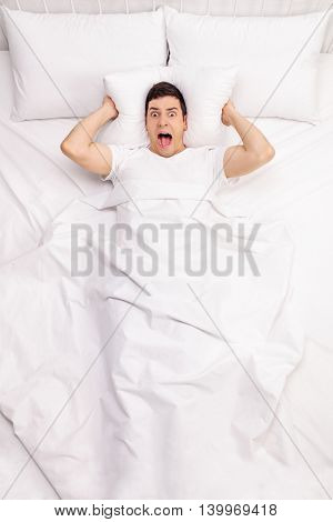 Vertical shot of a frustrated man suffering from insomnia and lying in a bed