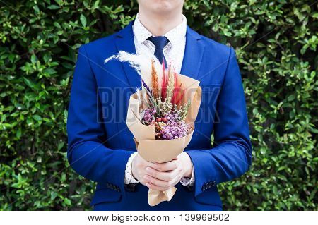 Young Man In Fashionable Suit Holding Hipster Hand-made Bouquet