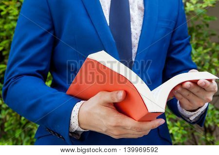 Young Businessman Reading Book In Green Nature Background
