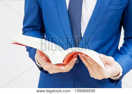 Young Businessman Reading Book In White Isolated Background