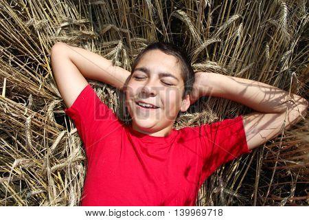 boy lies in wheat field in the summer
