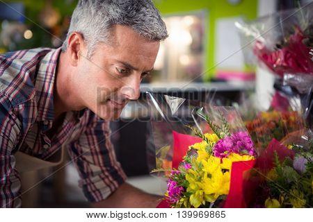 Close-up of male florist arranging bouquet of flower at his flower shop