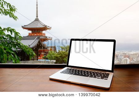 Laptop with blank screen on table. japan temple background