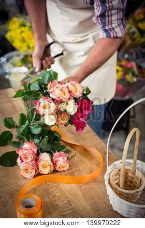 Mid section of male florist preparing bouquet of flower at his flower shop