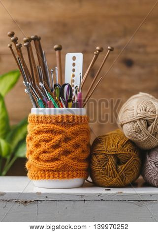 Jar with knitted cover holding different sized knitting needles and crochet hooks.
