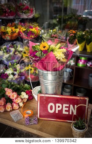Open signboard on a wooden table at flower shop