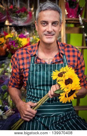 Portrait of male florist holding bunch of flowers at his flower shop