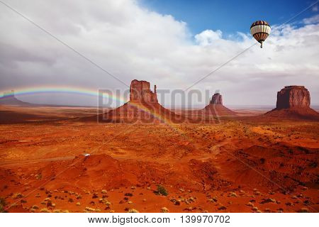 Huge balloon flies over Red Desert Navajo, USA. The picturesque rainbow crosses some rocks -