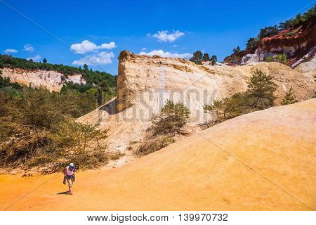 The elderly woman photographs landscape. Orange and red picturesque hills in Roussillon