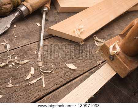 Old used carpenter tools on a wooden workbench