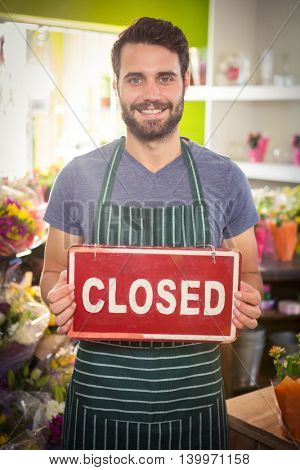 Portrait of male florist holding closed signboard at his flower shop